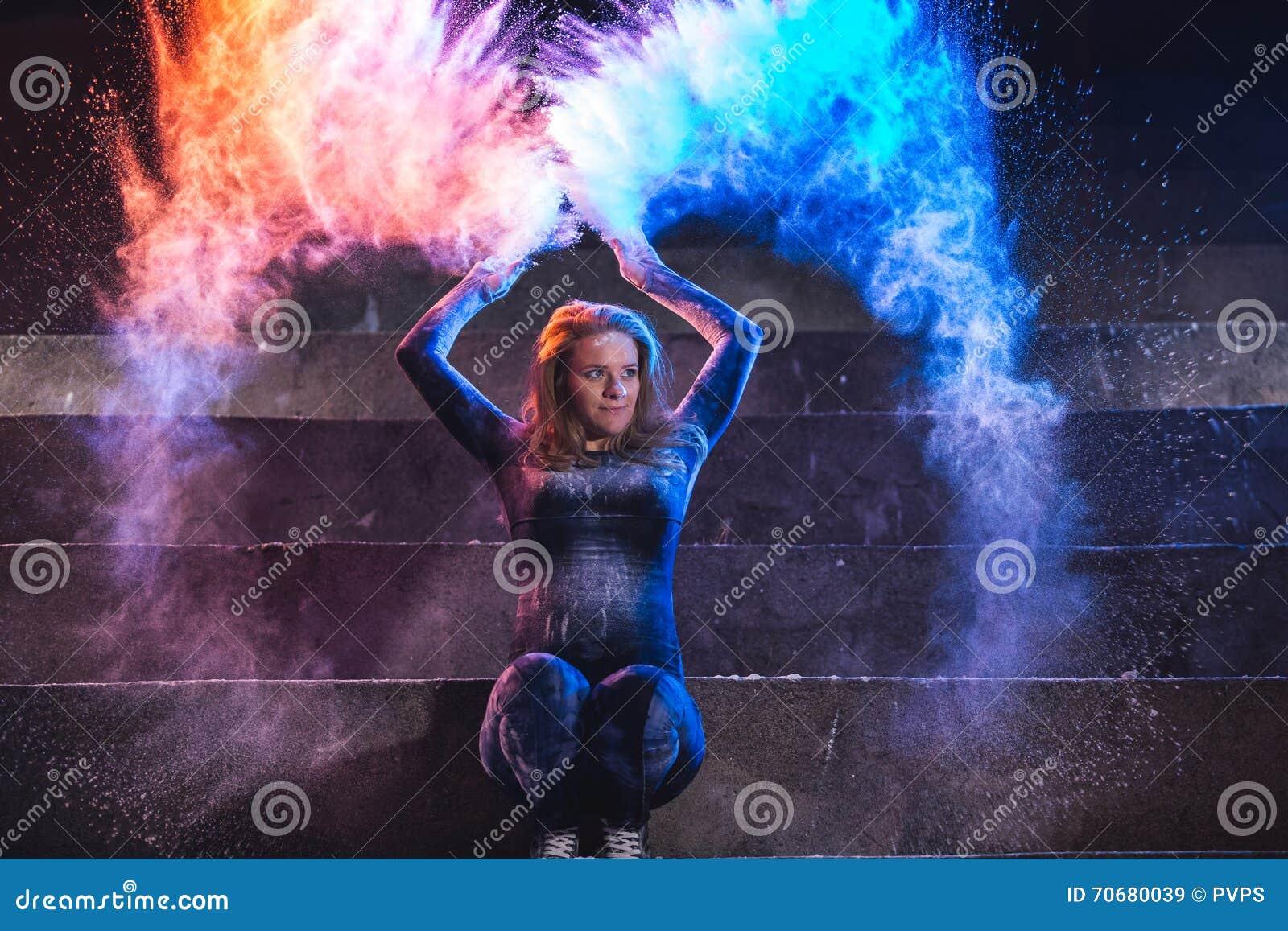 Kast och dans för ung kvinna med färgpulver på mörk bakgrund