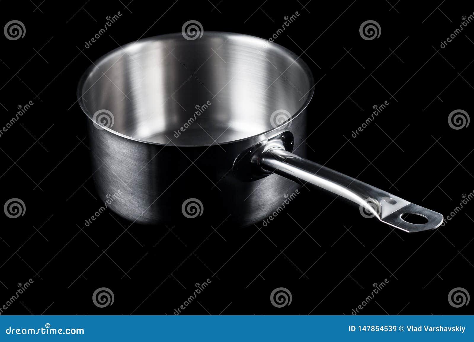 Kastrull med redskap för handtagrostfritt stålicke-pinne matlagning på en svart bakgrund, isolat