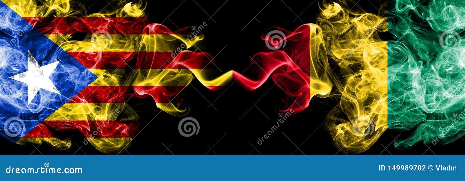Katalonien gegen Guinea, guineische Rauchflaggen nebeneinander gesetzt Dicke farbige seidige Rauchflaggen von Katalonien und von