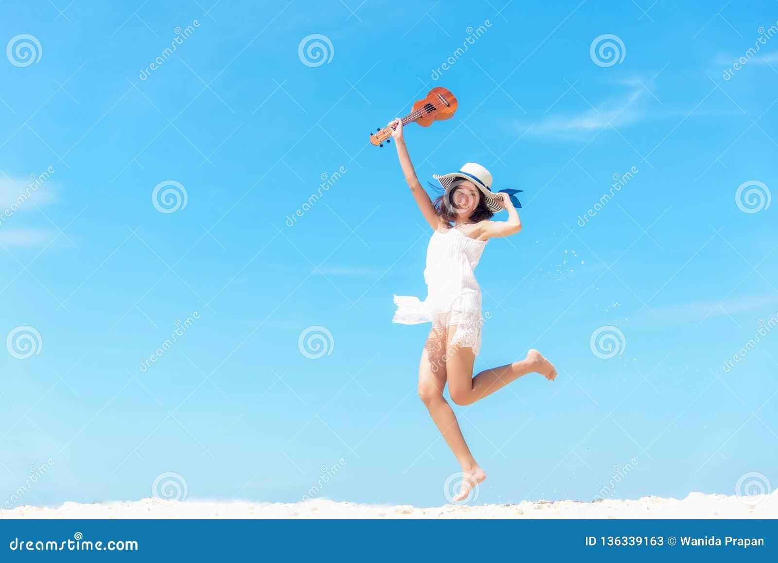 Katya krasnodar夏天领土假期 放松和跳跃与在海滩的尤克里里琴的嗅到的亚裔妇女,很愉快和豪华在假日夏天,