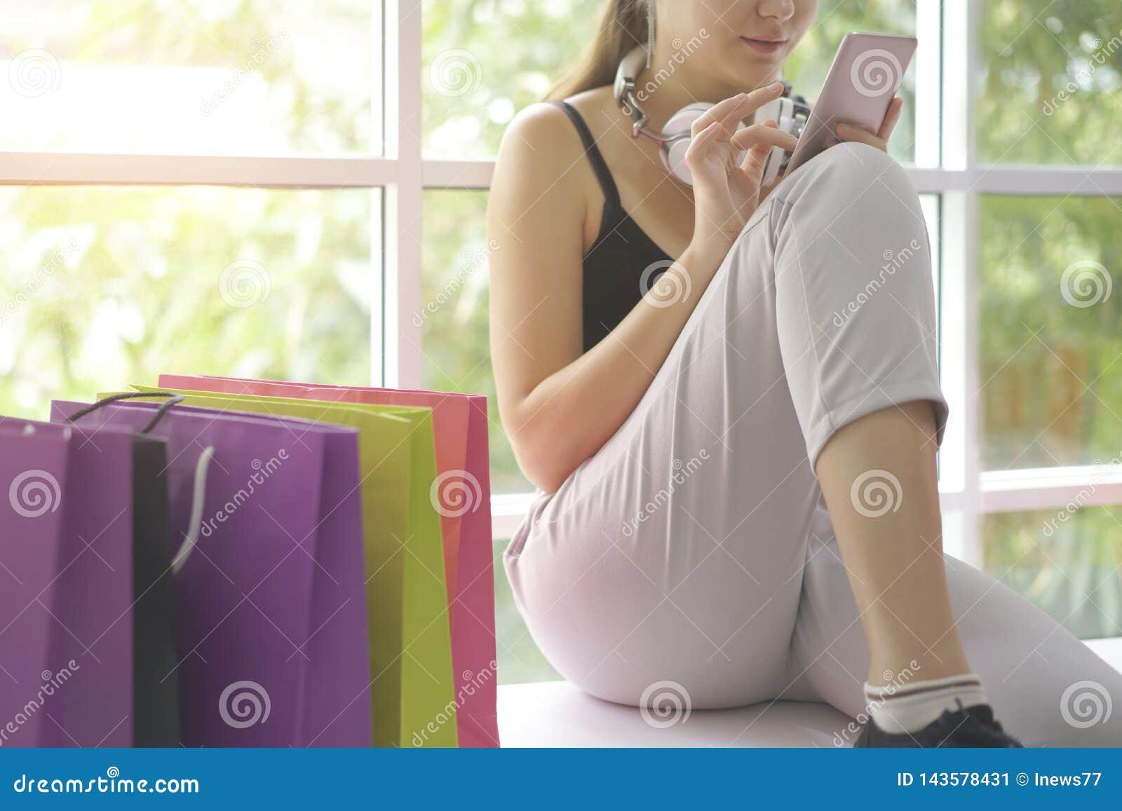 Kaukasisch meisje die online met de winkel van smartphoneinternet, e-commercewebsite op mobiel winkelen