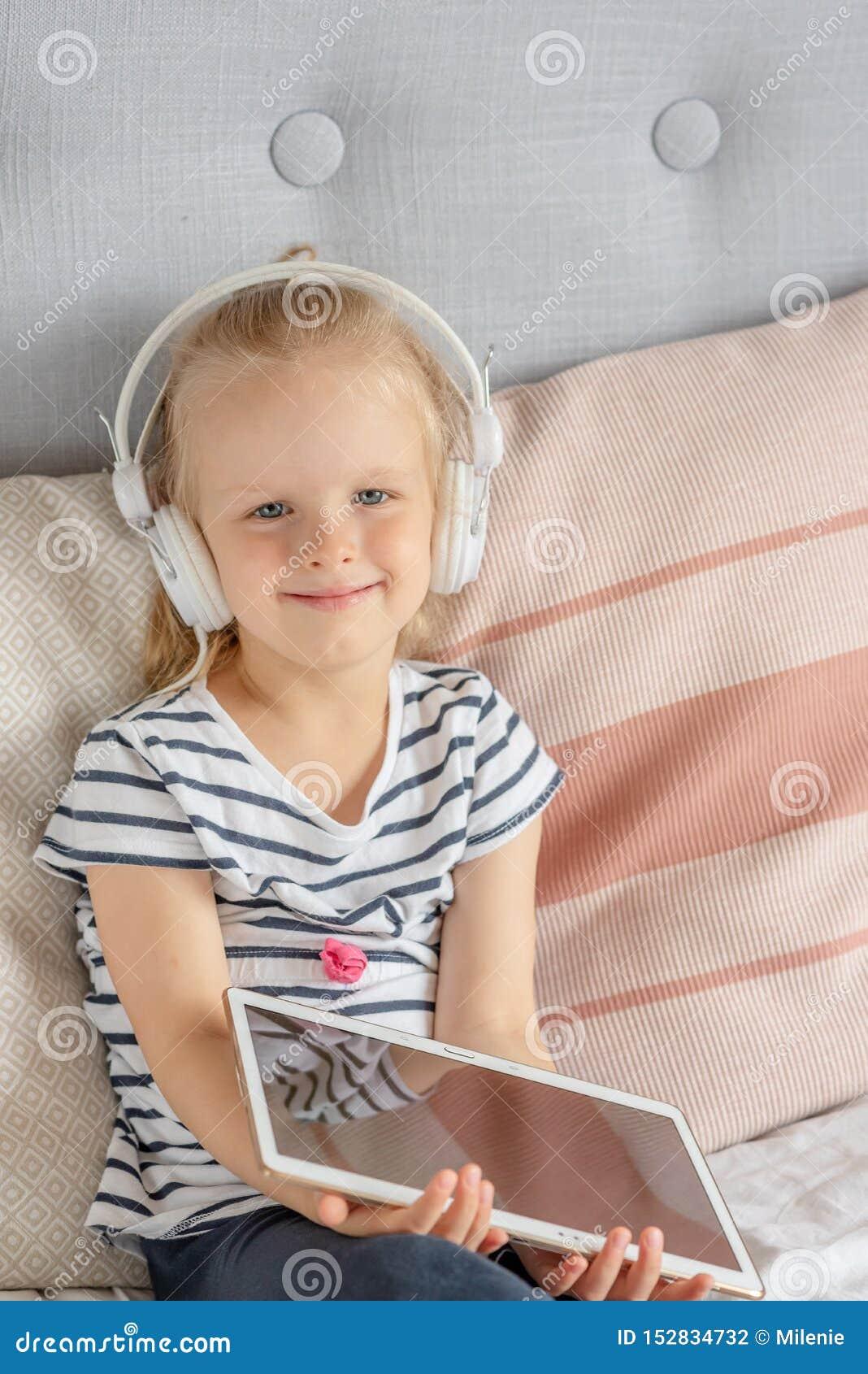 Kaukasisch Meisje in Hoofdtelefoon het Letten op Tablet in Bed