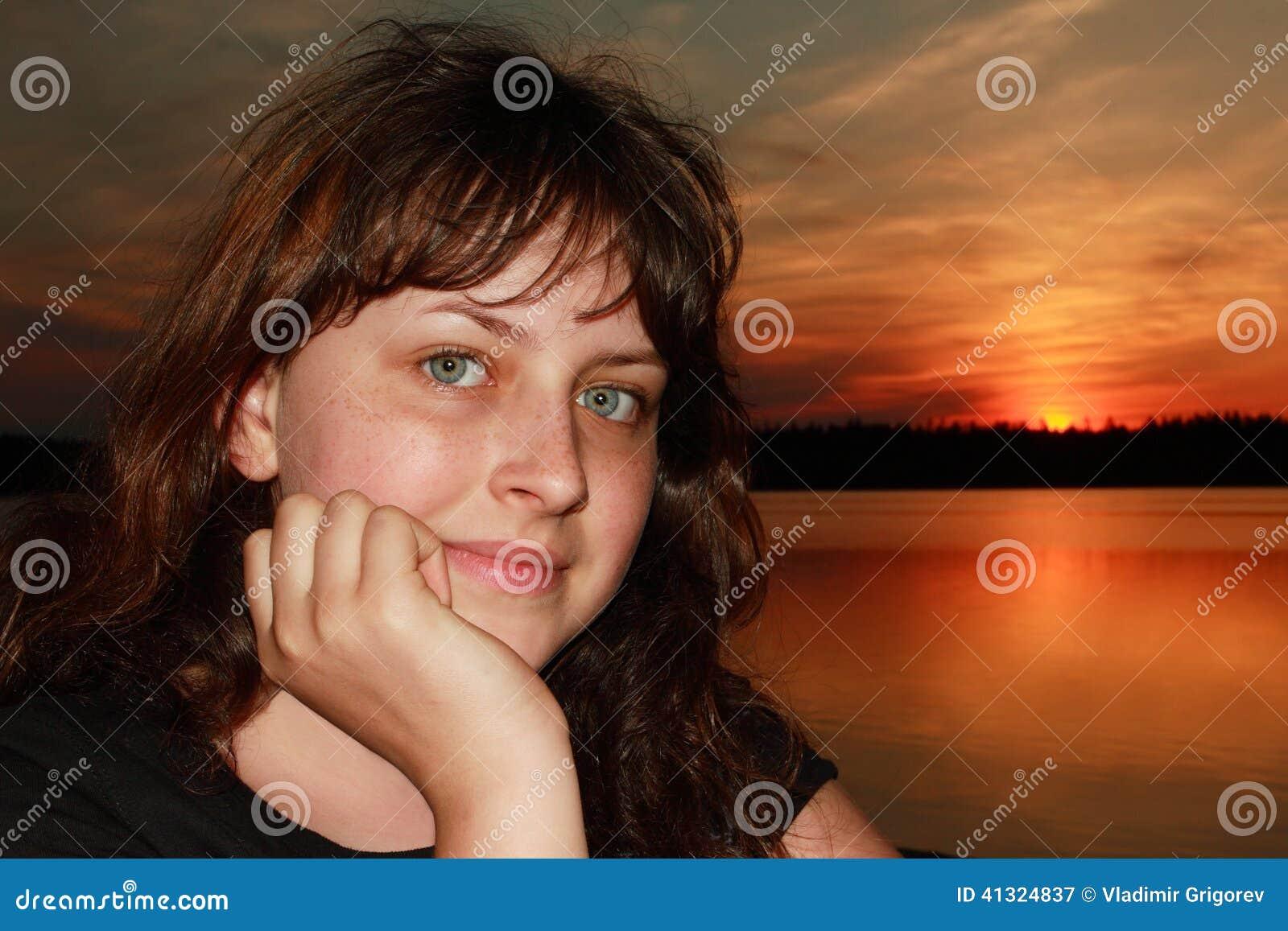 Kaukasisch oud meisje 13 jaar, close-up op zonsondergangachtergrond
