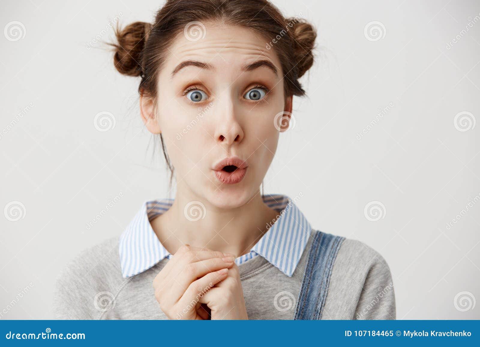 Kaukasische Frau, die erstaunt schaut, Fäuste halten zusammengepreßt Attraktives weibliches wunderndes überrascht sein des Büroan