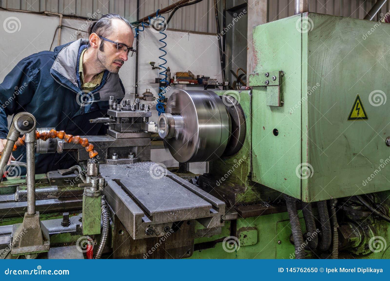 Kaukasische ingenieur die op het asblok van het draaien van draaibankmachine letten in fabriek