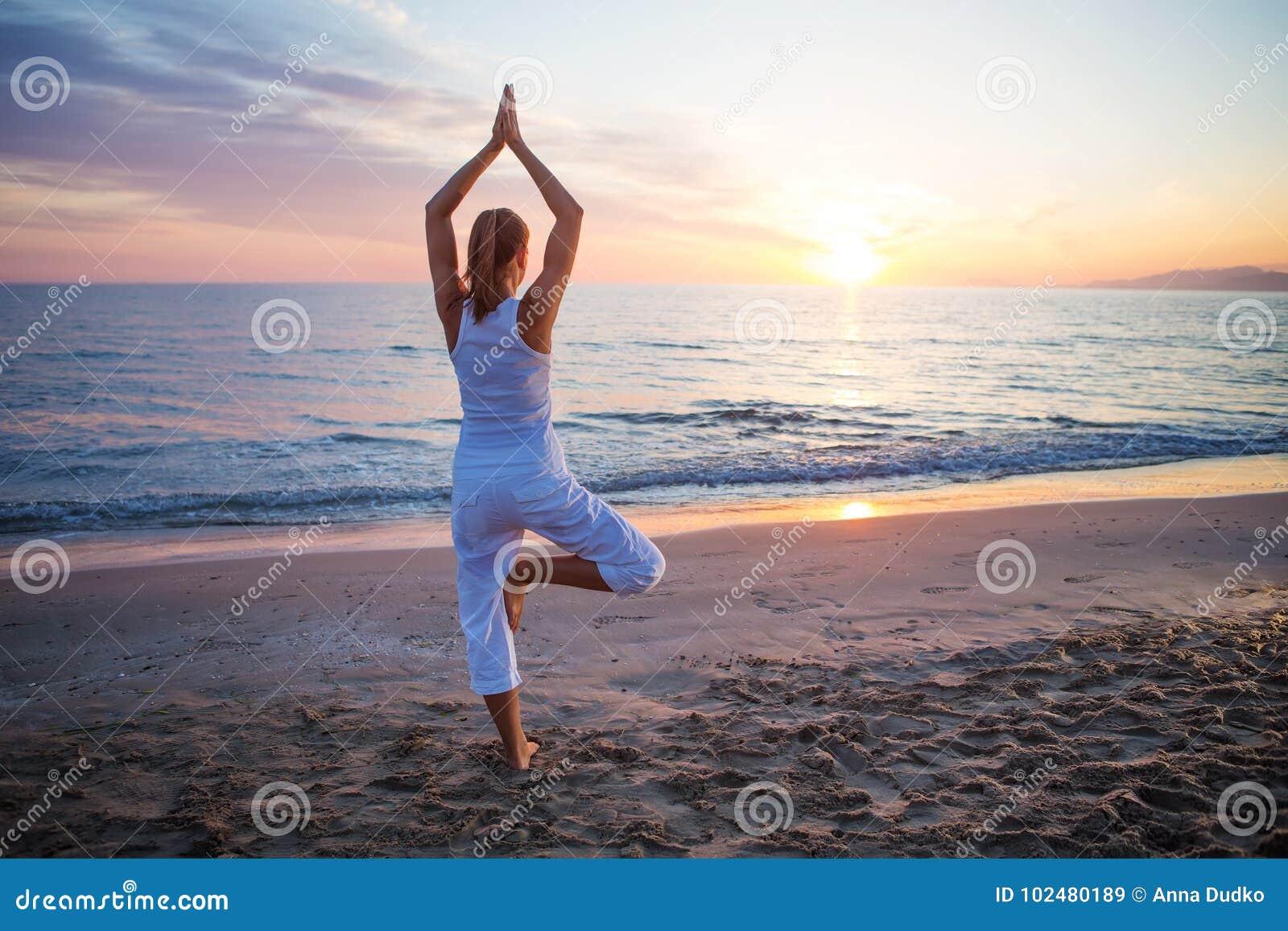 Kaukasische vrouw het praktizeren yoga bij kust