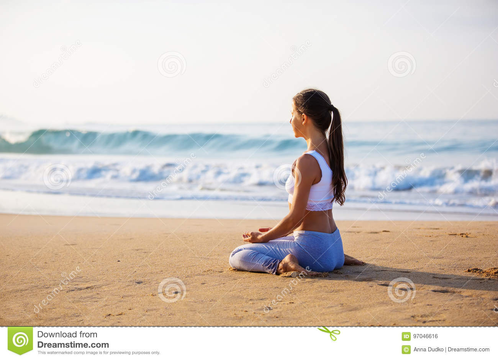 Kaukasische vrouw het praktizeren yoga bij kust van tropische oceaan
