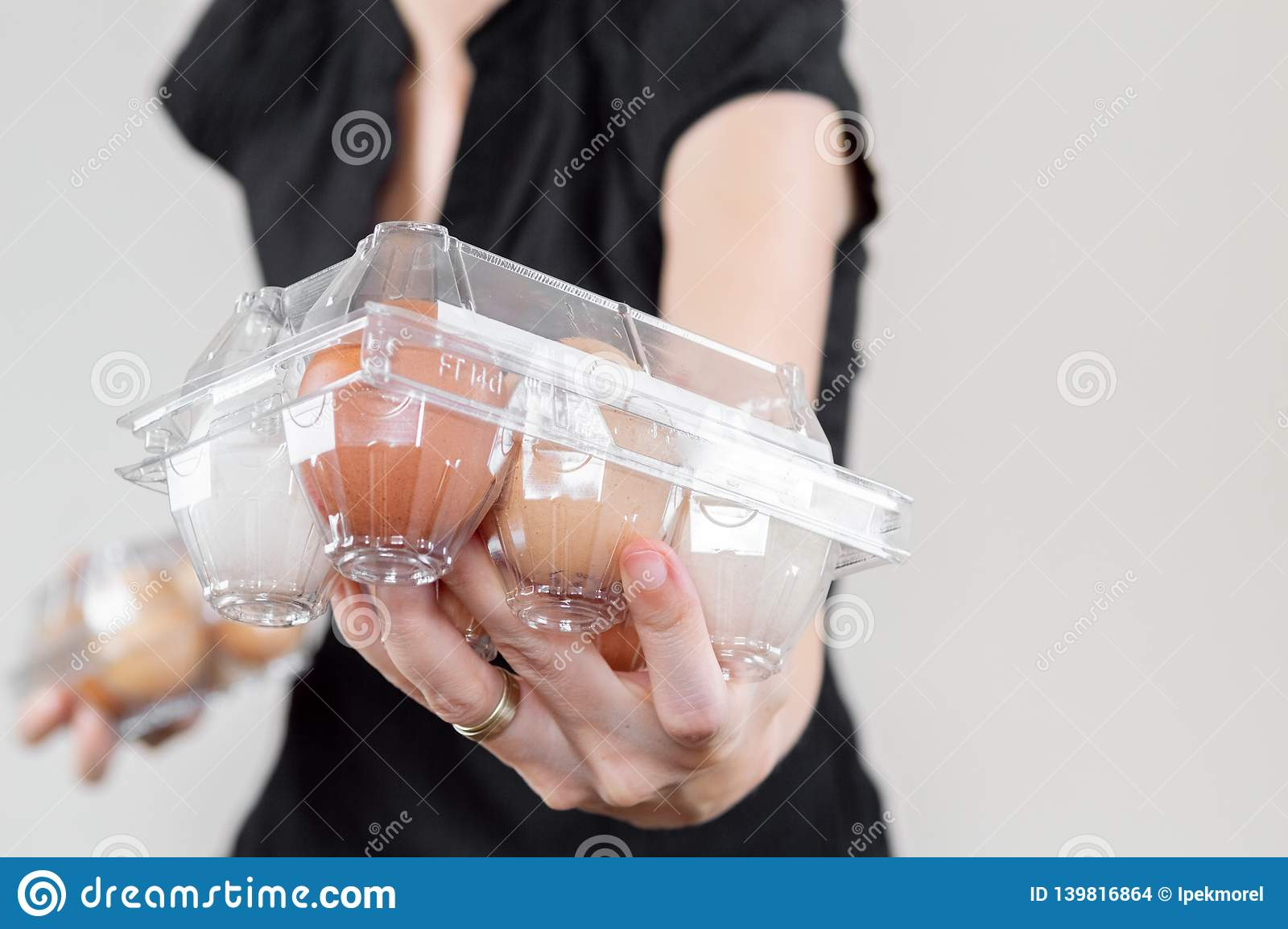 Kaukasische vrouw met zwart overhemd die een plastic hoogtepunt van de eidoos van kippeneieren tonen