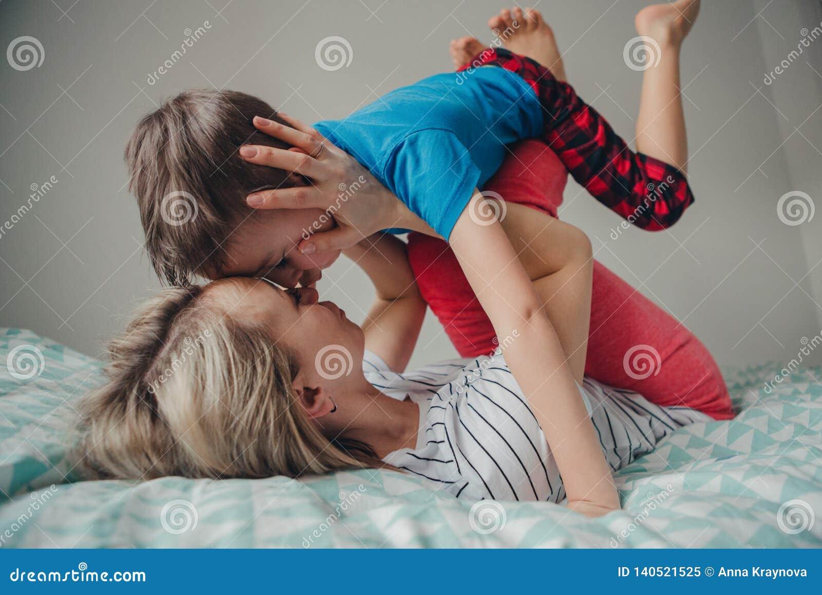 Kaukasischer Mutter- und Jungensohn, der zu Hause im Schlafzimmer spielt