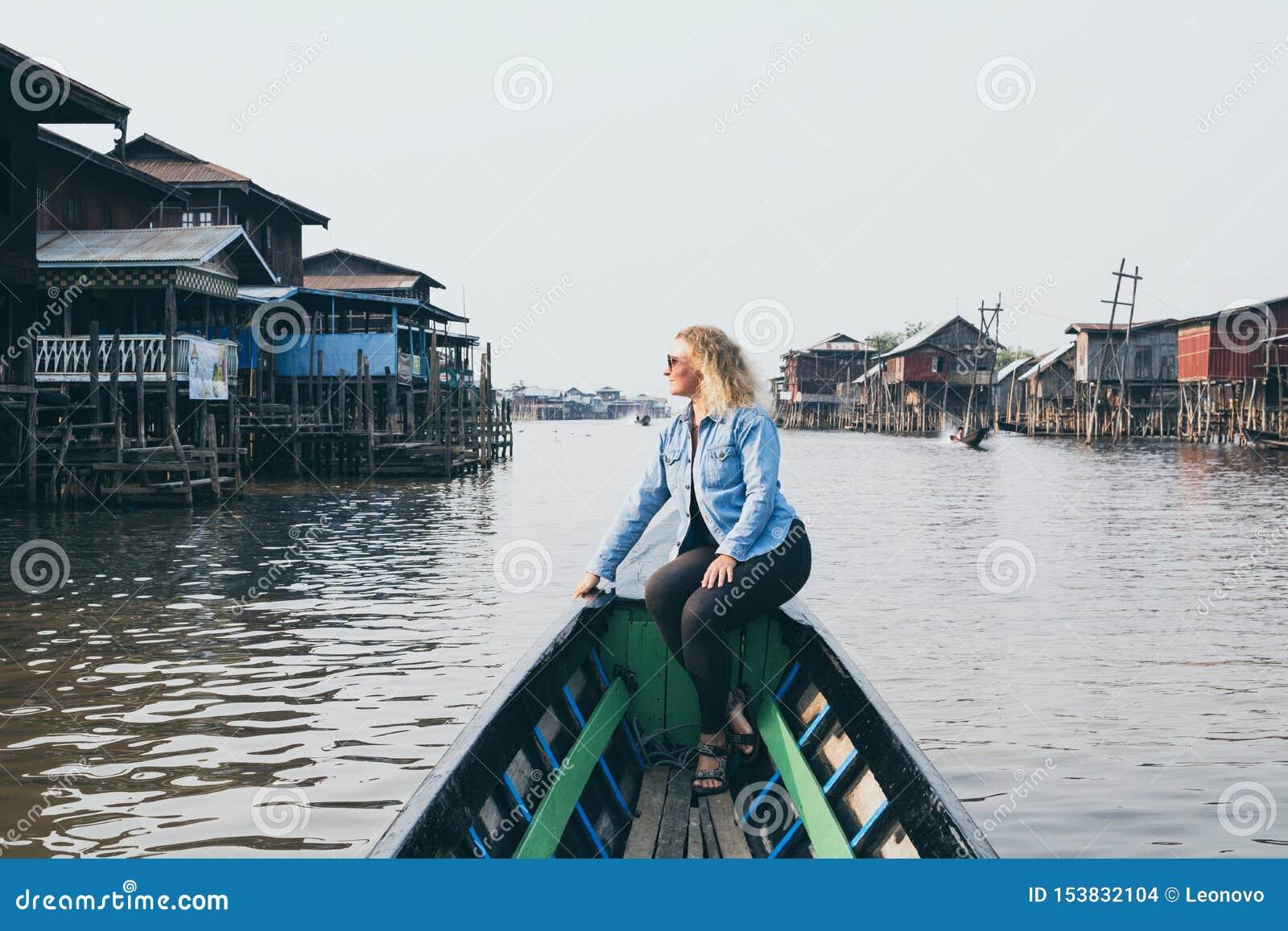Kaukaska blondynki kobieta ma łódkowatą przejażdżkę na Inle jeziorze, Myanmar