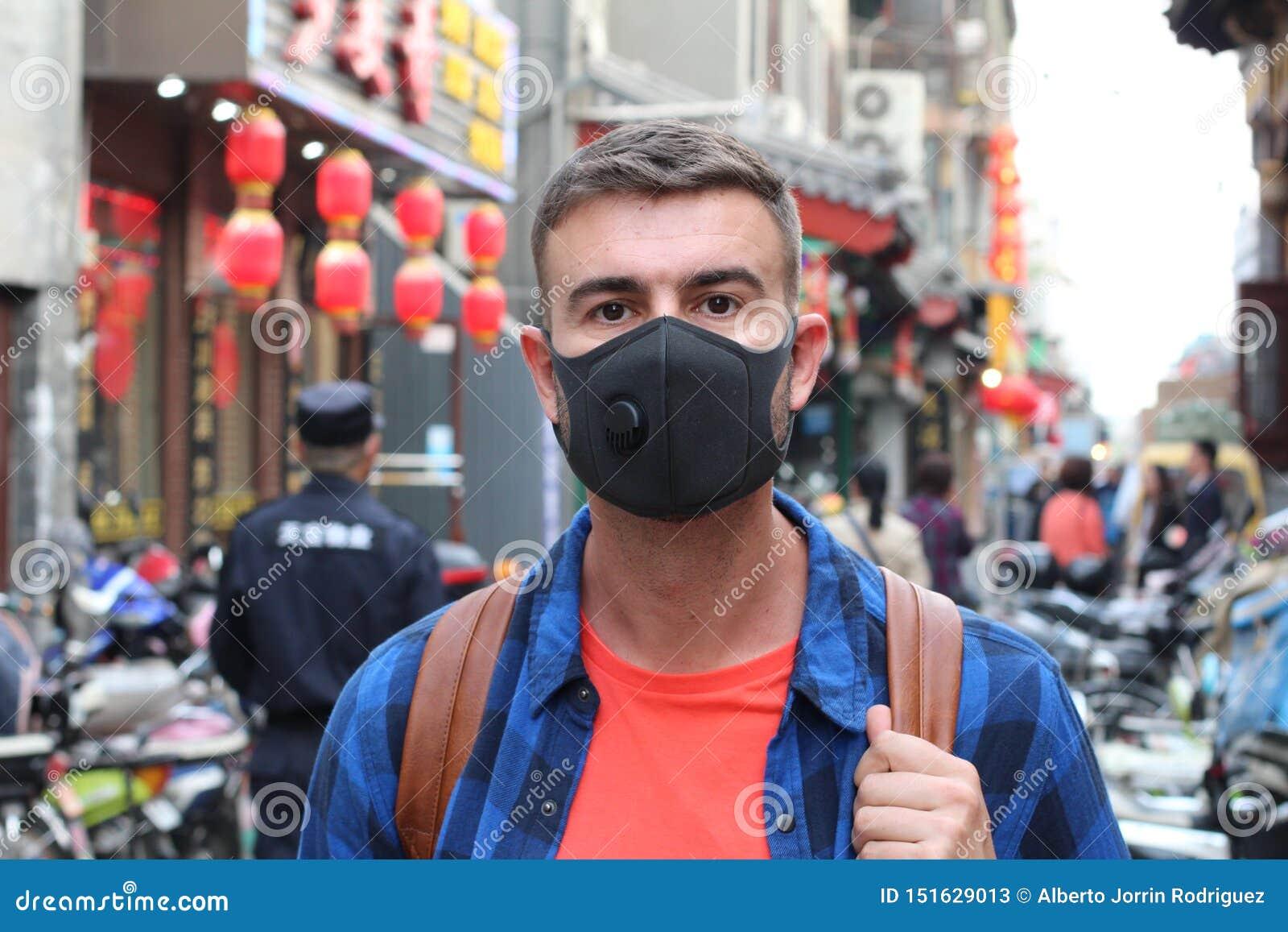 Kaukaski mężczyzna jest ubranym zanieczyszczenie maskę w Azja