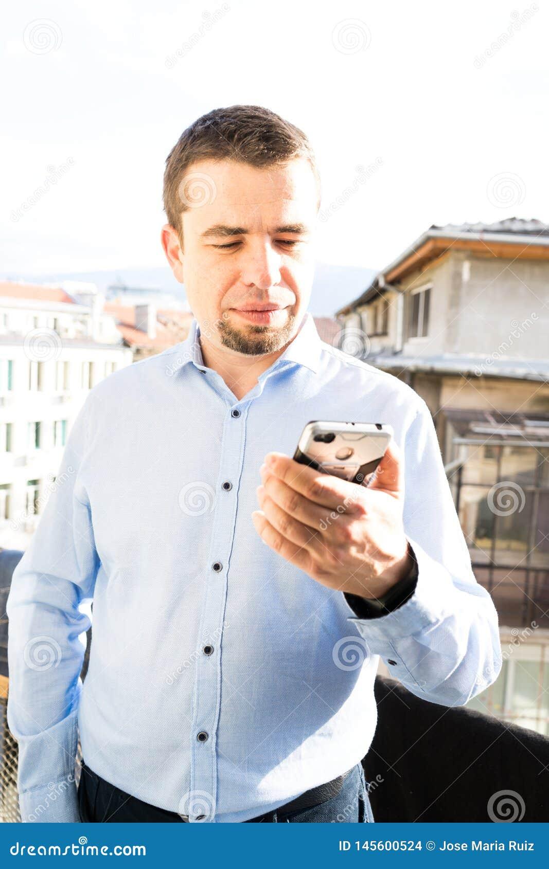 Kaukaski mężczyzna używa Mobil telefon w balkonie Portreta błękitny koszulowy młody przyglądający zmniejszający się ekran 3d sie?