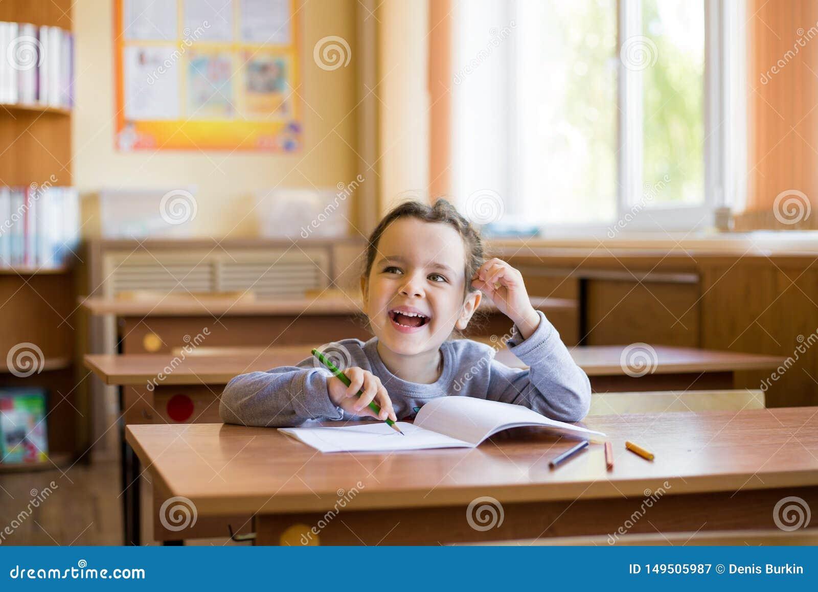 Kaukaski ma?y u?miechni?ty dziewczyny obsiadanie przy biurkiem w klasowym pokoju i zaczyna ostro?nie rysowa? w czystym notatniku