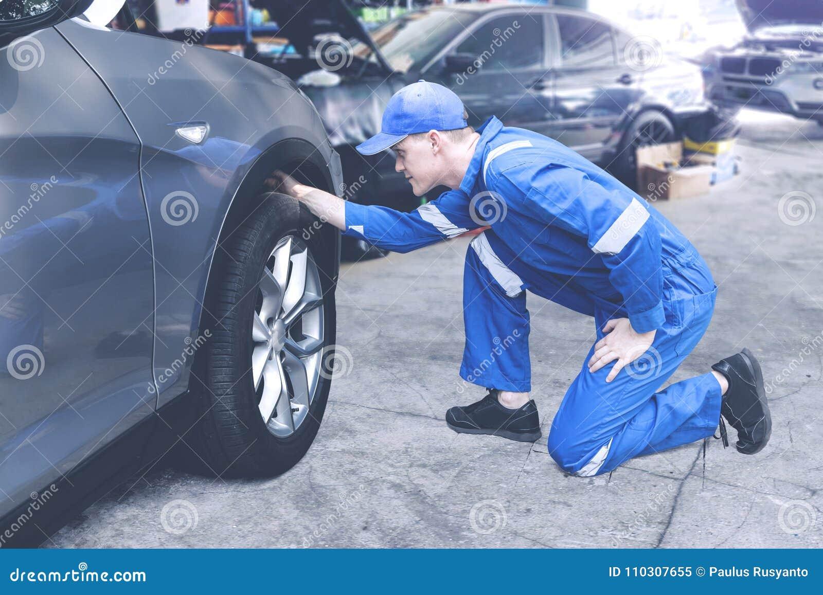 Kaukaski mechanik sprawdza na oponie w warsztacie