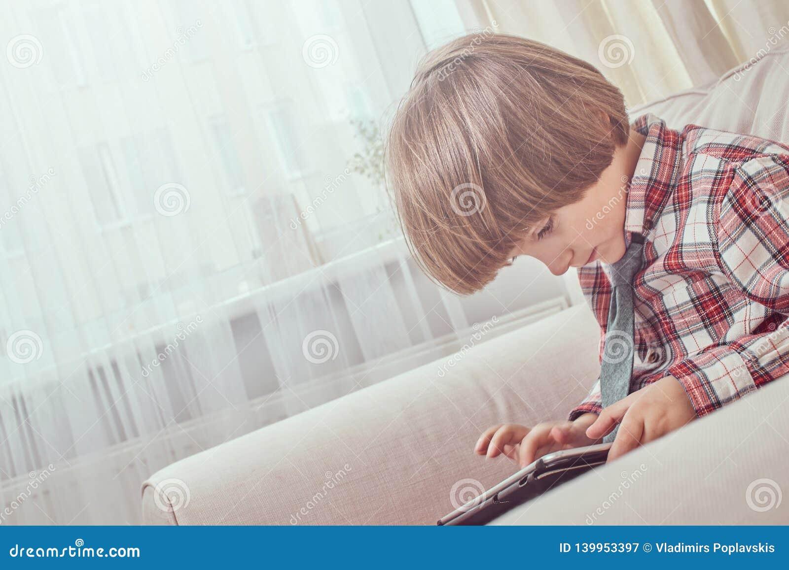 Kaukaski uczeń jest ubranym w kratkę koszula z krawatem używać cyfrowego pastylki obsiadanie na leżance w domu
