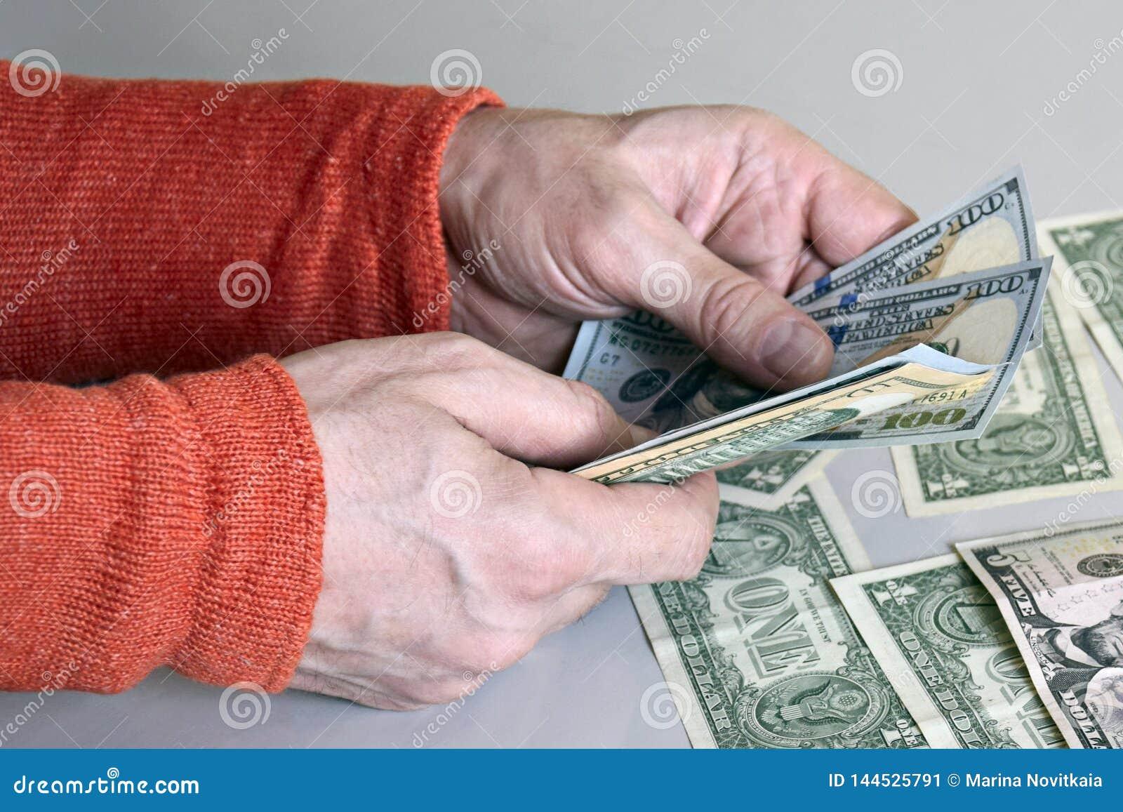 Kaukaskie mężczyzna ręki liczy dolarowych banknoty