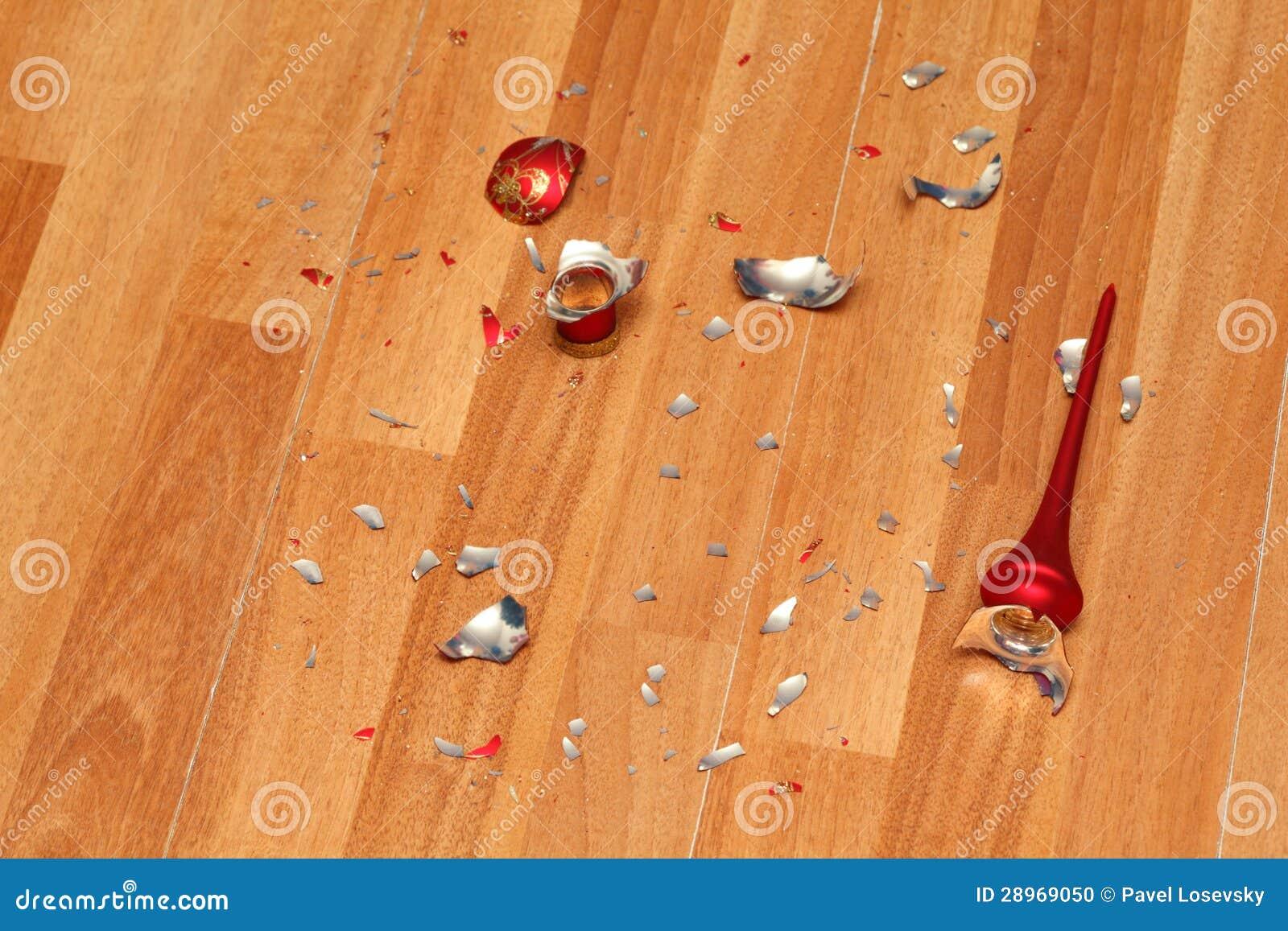 Kawałeczki zdruzgotana czerwona Bożenarodzeniowa piłka na podłoga.