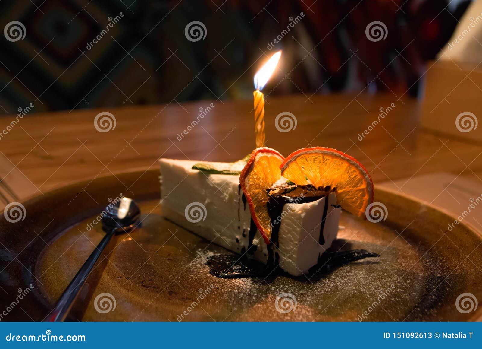 Kawałek tort z świeczkami, dla urodziny z pomarańczami