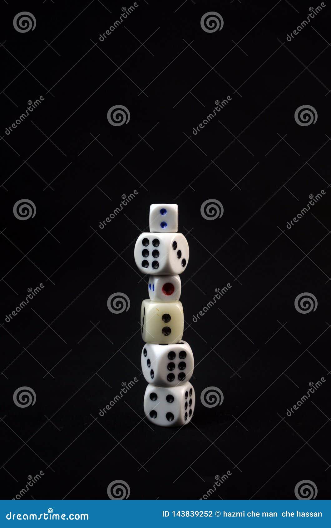 Kawałki białe kostki do gry na czarnym tle