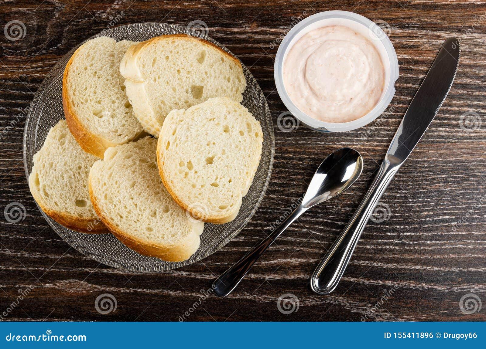 Kawałki chleb w talerzu, słój z krill pastą, łyżka, nóż na drewnianym stole Odg?rny widok