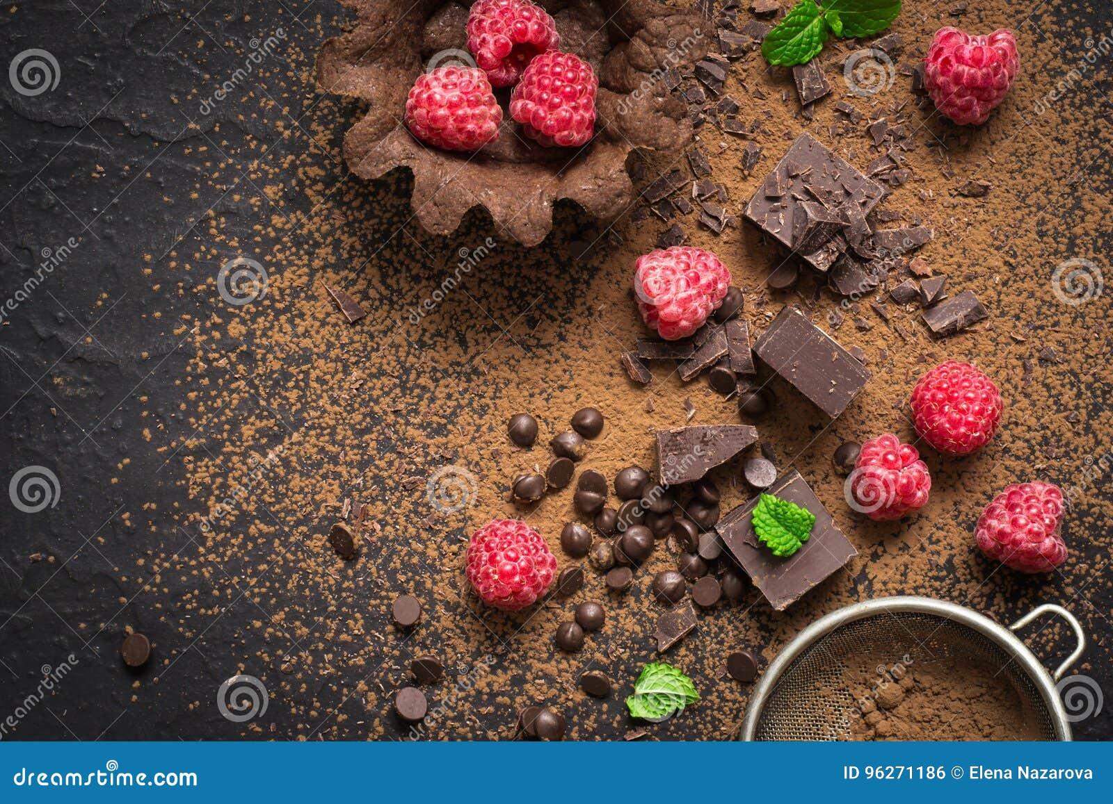 Kawałki czekolada, świeże malinki i tartlets, przygotowanie Karmowy deserowy tło
