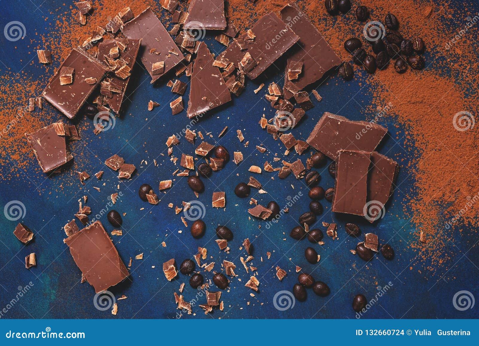 Kawałki czekolada, piec kawowe fasole i kakaowy proszek na błękitnym tle, Odgórny widok, mieszkanie nieatutowy