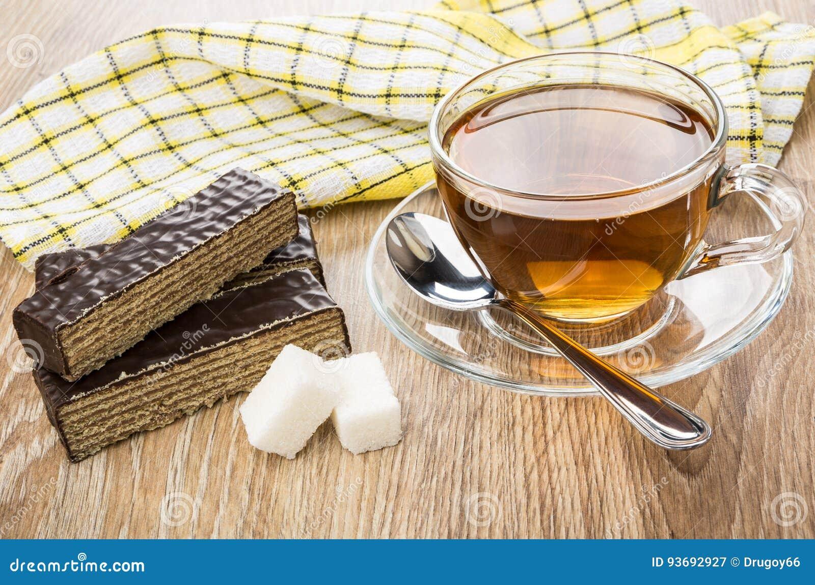 Kawałki czekoladowy gofra tort, filiżanka herbata, cukier