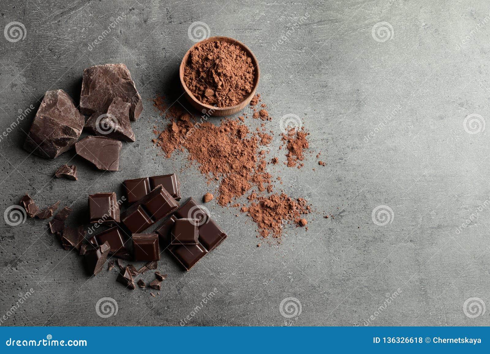 Kawałki czekoladowy i kakaowy proszek na popielatym tle