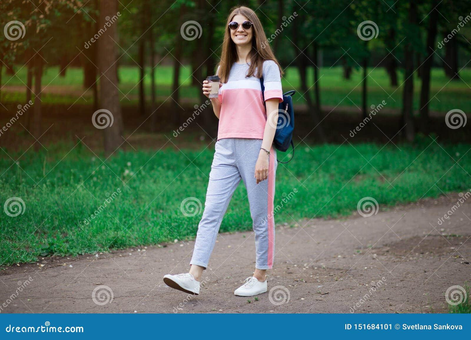 Kawa dalej i?? Piękna młoda kobieta trzyma filiżankę i ono uśmiecha się w okularach przeciwsłonecznych podczas gdy chodzący