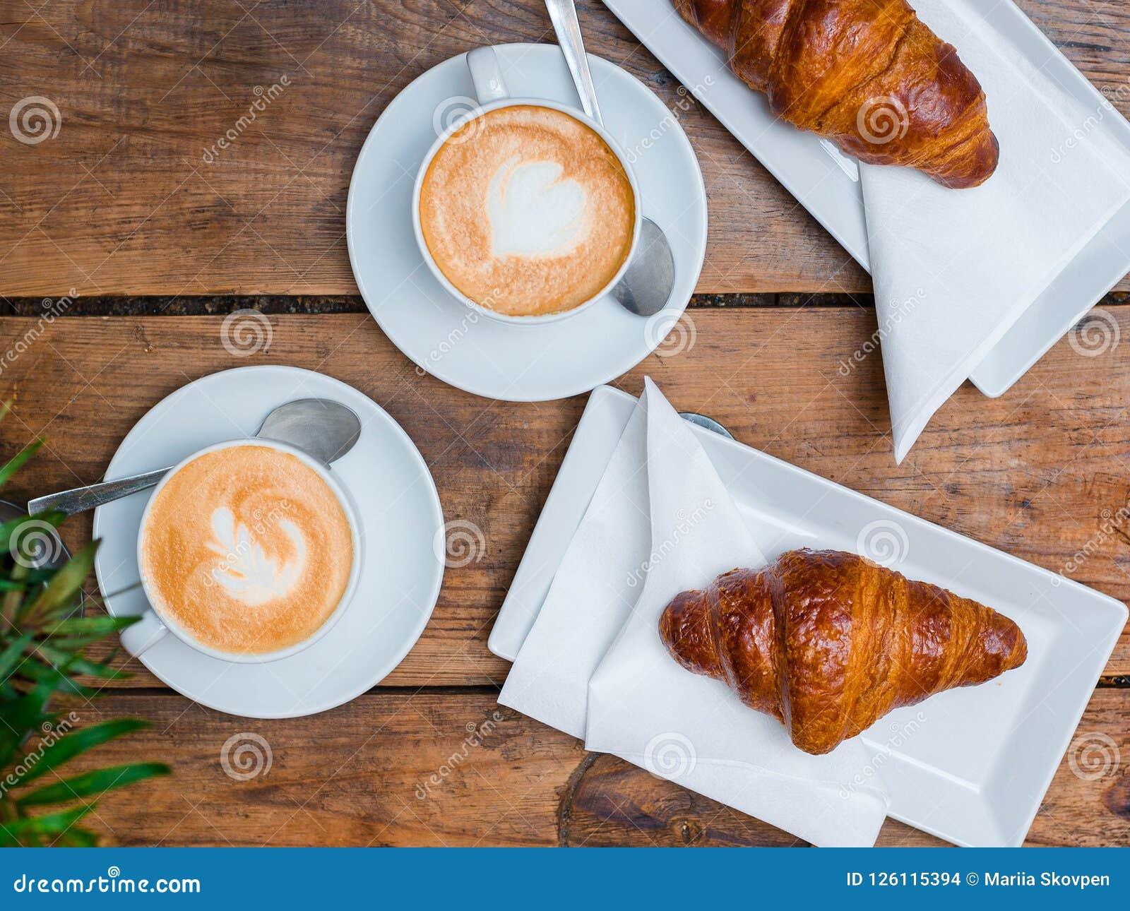 Kawa i croissant dla śniadaniowej Cukiernianej kultury Croissants z dwa filiżanek małym cappuccino z obrazkiem, odgórny widok