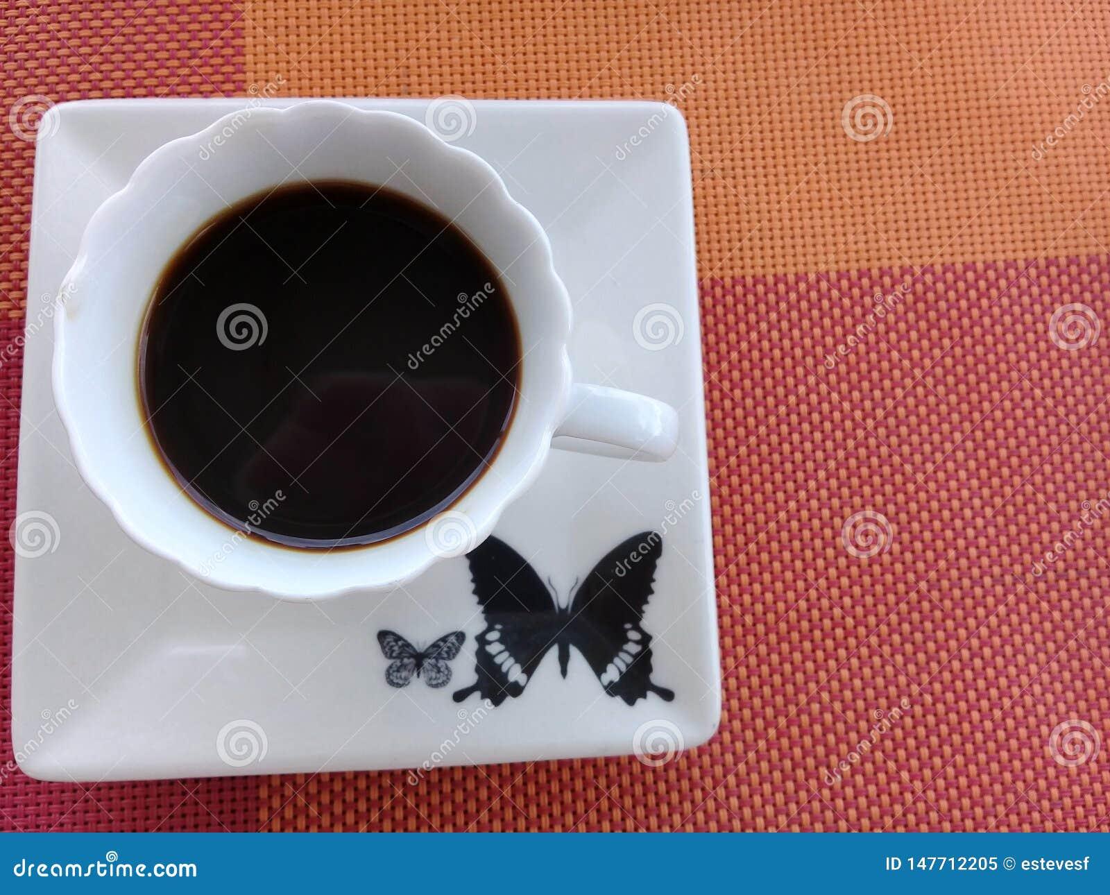 Kawa na górze spodeczka z motylim projektem