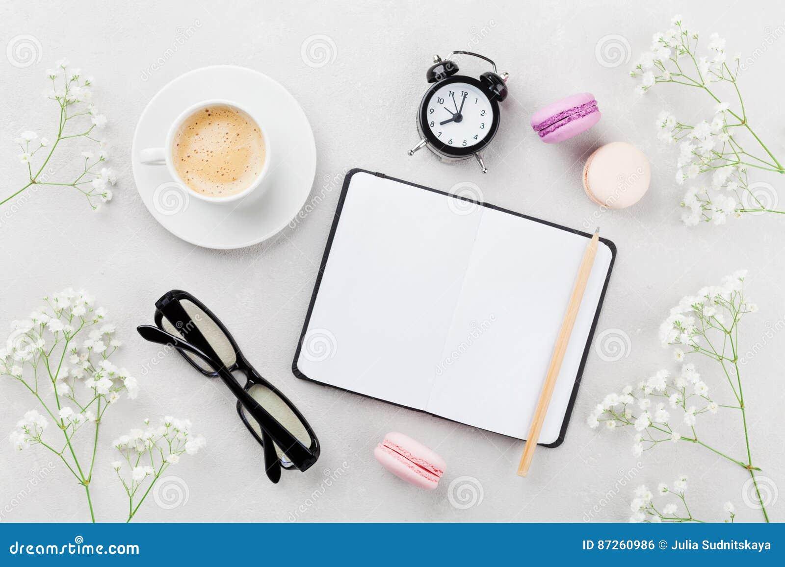 Kawa, tortowy macaron, notatnik, eyeglasses, budzik i kwiat dla śniadania na stołowym odgórnym widoku, Kobiety pracujący biurko M