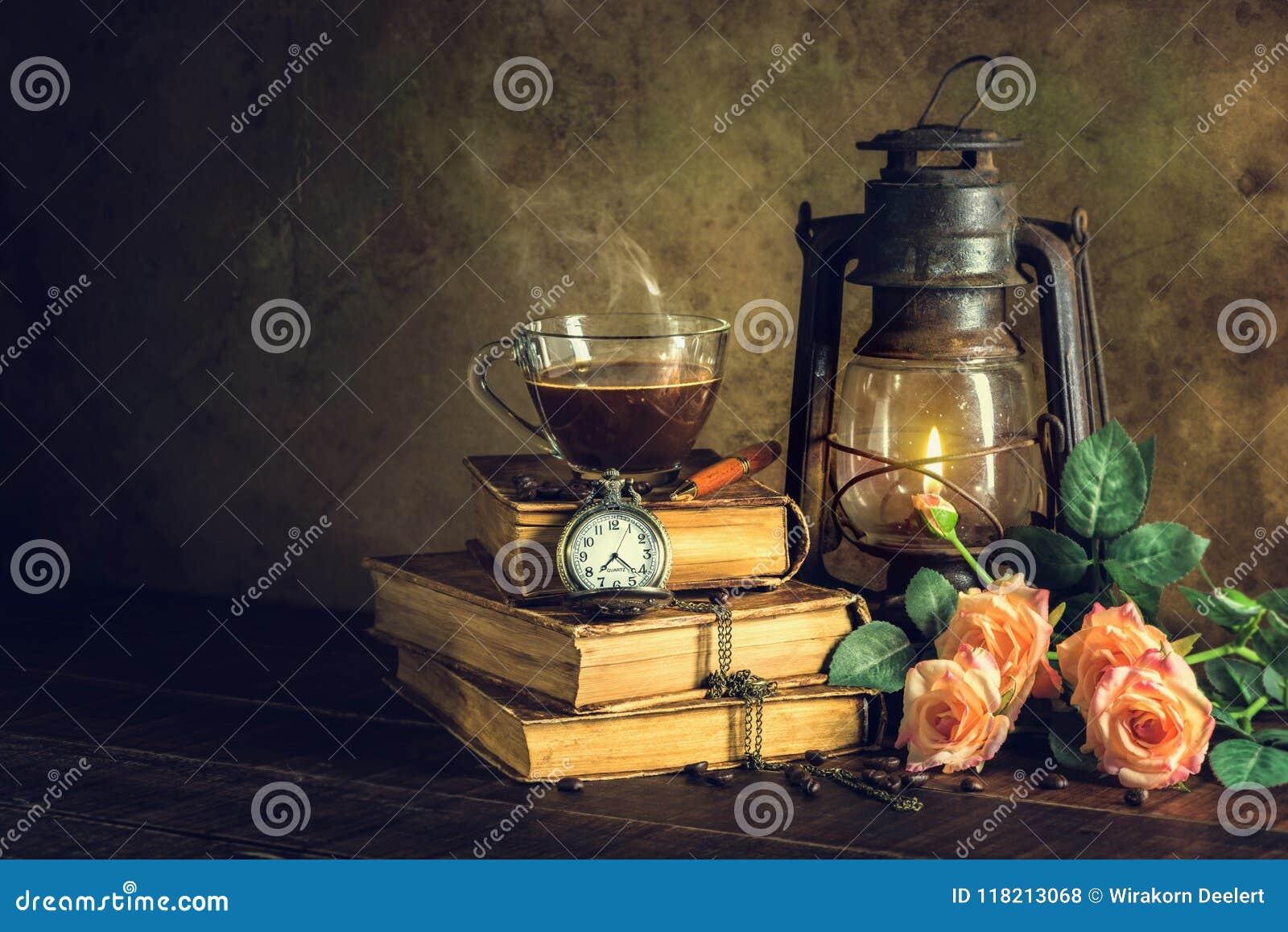 Kawa w filiżanki szkle na starych książkach i zegarowy rocznik z nafty lampą oliwimy latarniowego palenie z jarzeniowym miękkim ś