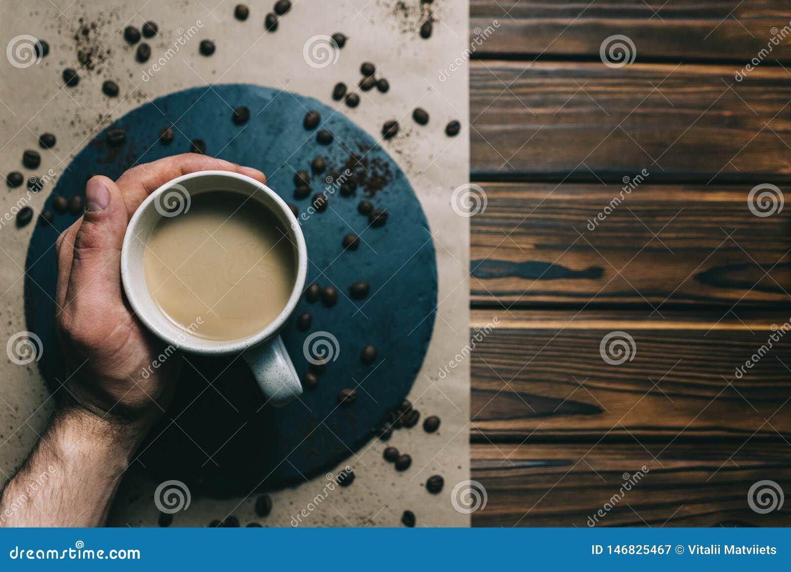 Kawa w grater z filiżanką w ręce na ciemnym tle z śmietanką