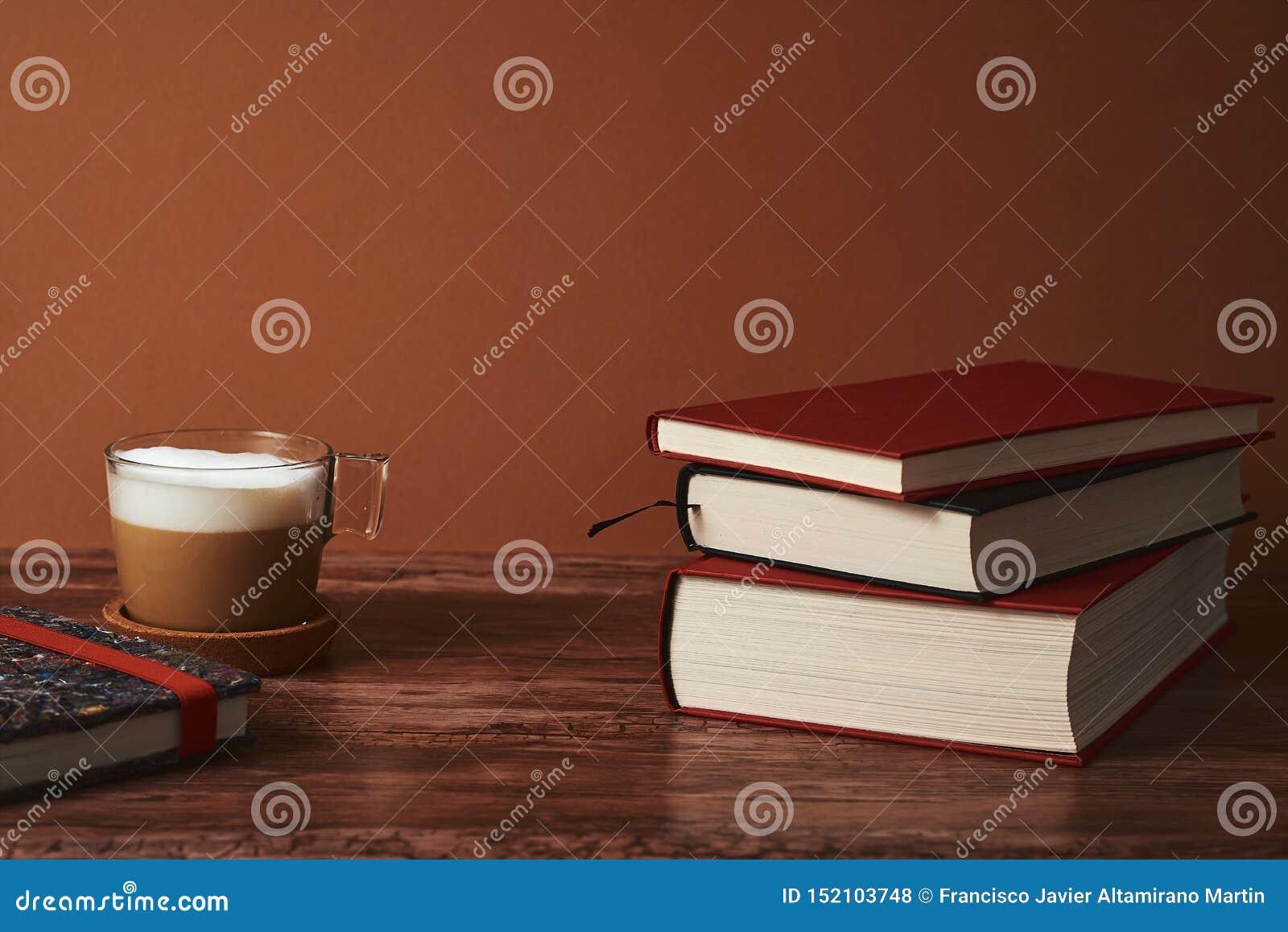 Kawa z mlekiem i książkami na brązu drewnianym stole