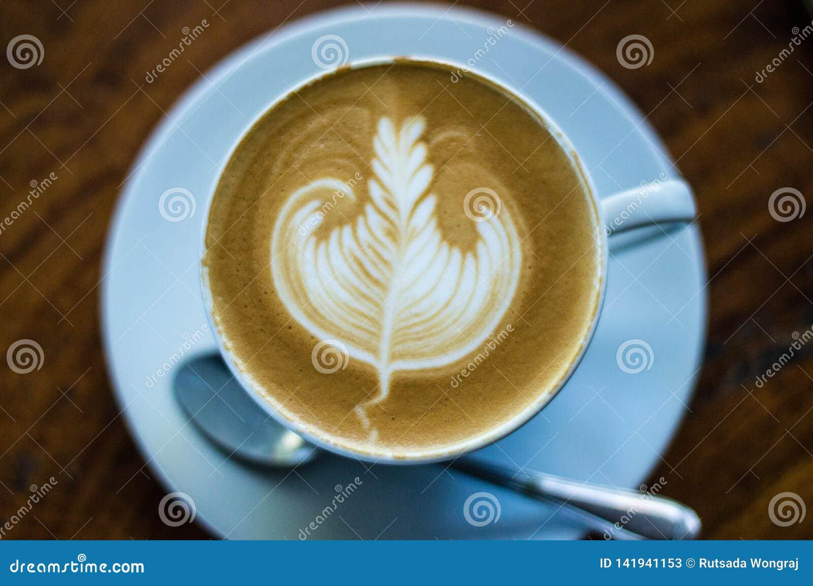 Kawowa Latte sztuka, liść na białym talerzu