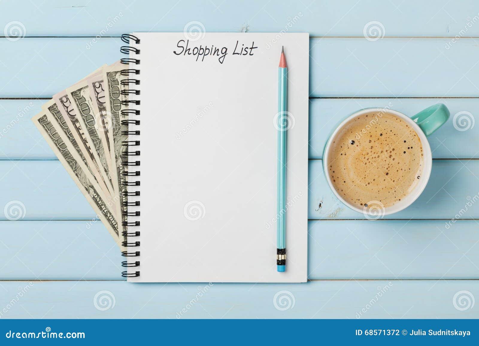 Kawowy kubek i notatnik z listą zakupów i gotówka pieniądze dolarem na błękitnym wieśniaka stole