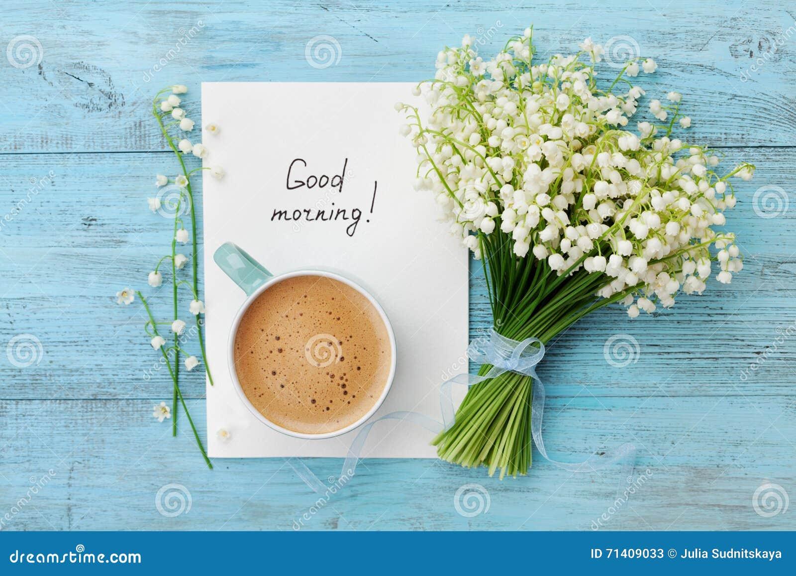Kawowy kubek z bukietem kwiat leluja doliny i notatek dzień dobry na turkusowym wieśniaka stole od above