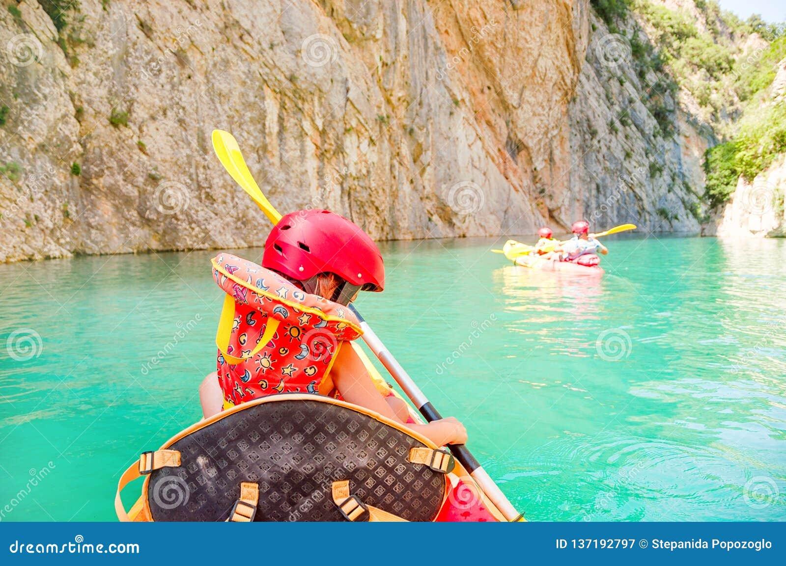 Kayak della bambina sul bello fiume, divertendosi e godendo degli sport all aperto Sport acquatico e divertimento di campeggio