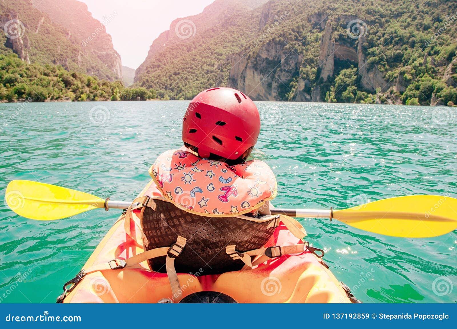 Kayak della bambina sul bello fiume, divertendosi e godendo degli sport all aperto Sport acquatico e divertimento di campeggio Go