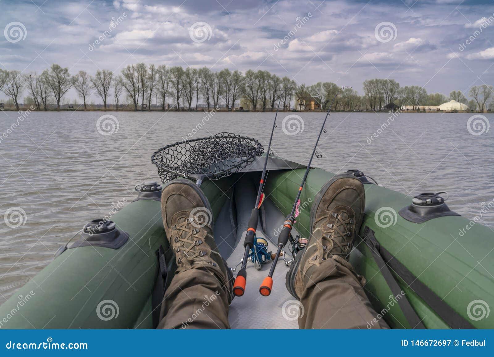Kayak fishing at lake. Legs of fisherman on inflatable boat with fishing tackle
