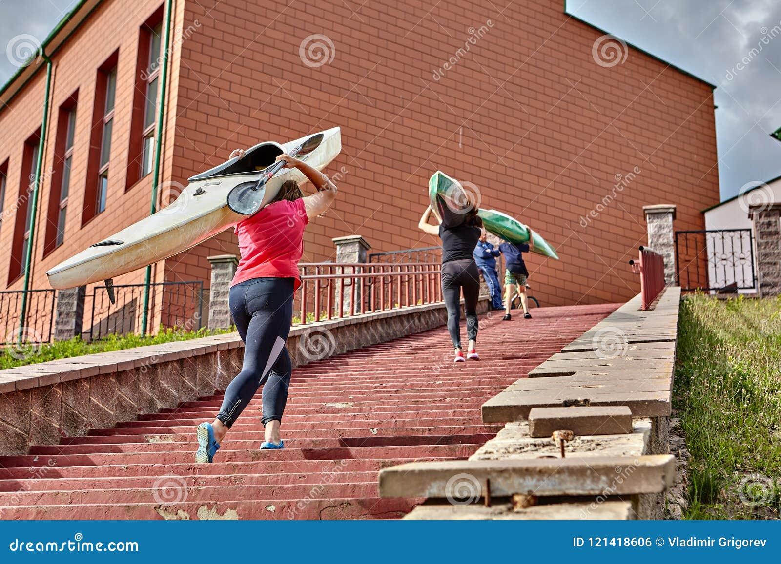 Kayakers går uppför trappan med kajaker på skuldror, når de har rott tra