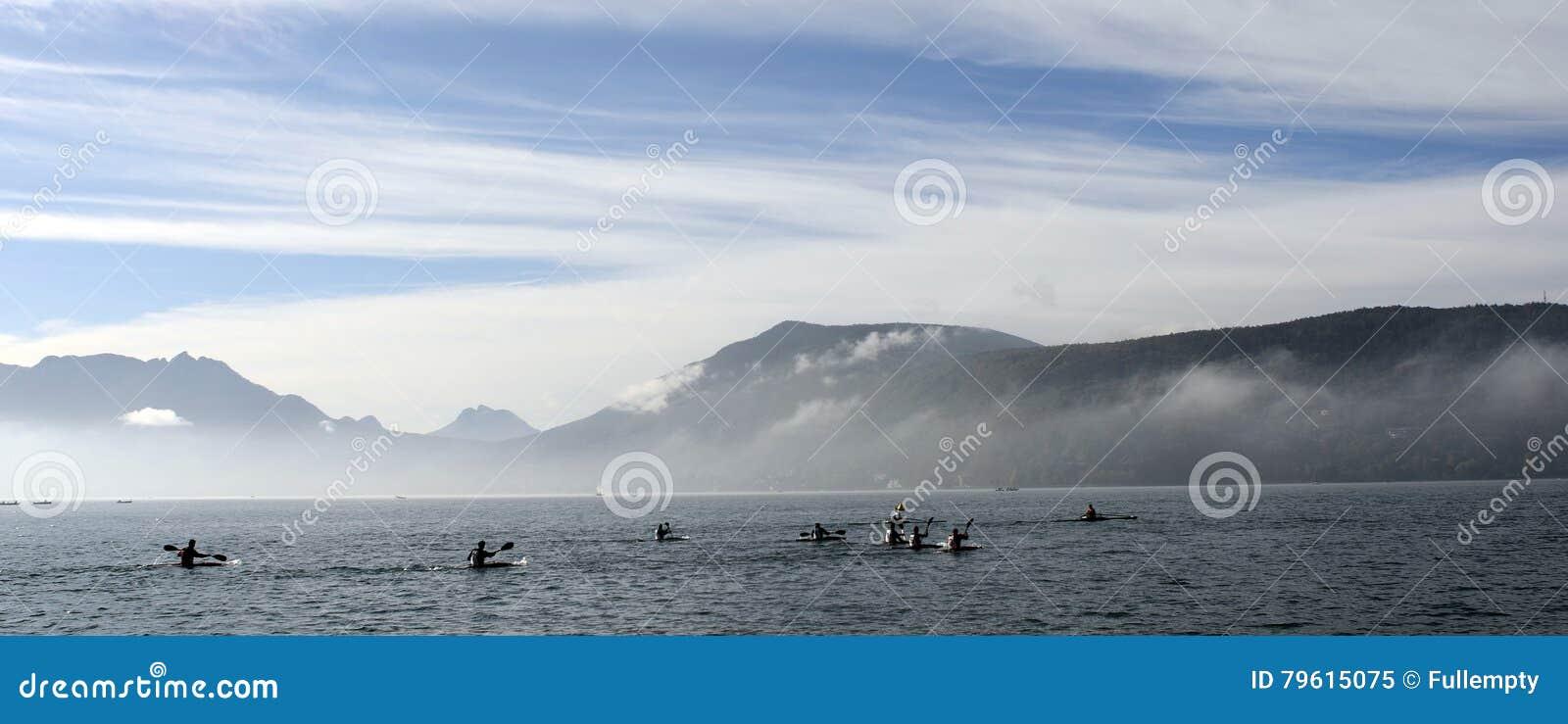 Kayakers no caiaque e na canoa que fazem a raça no lago Annecy