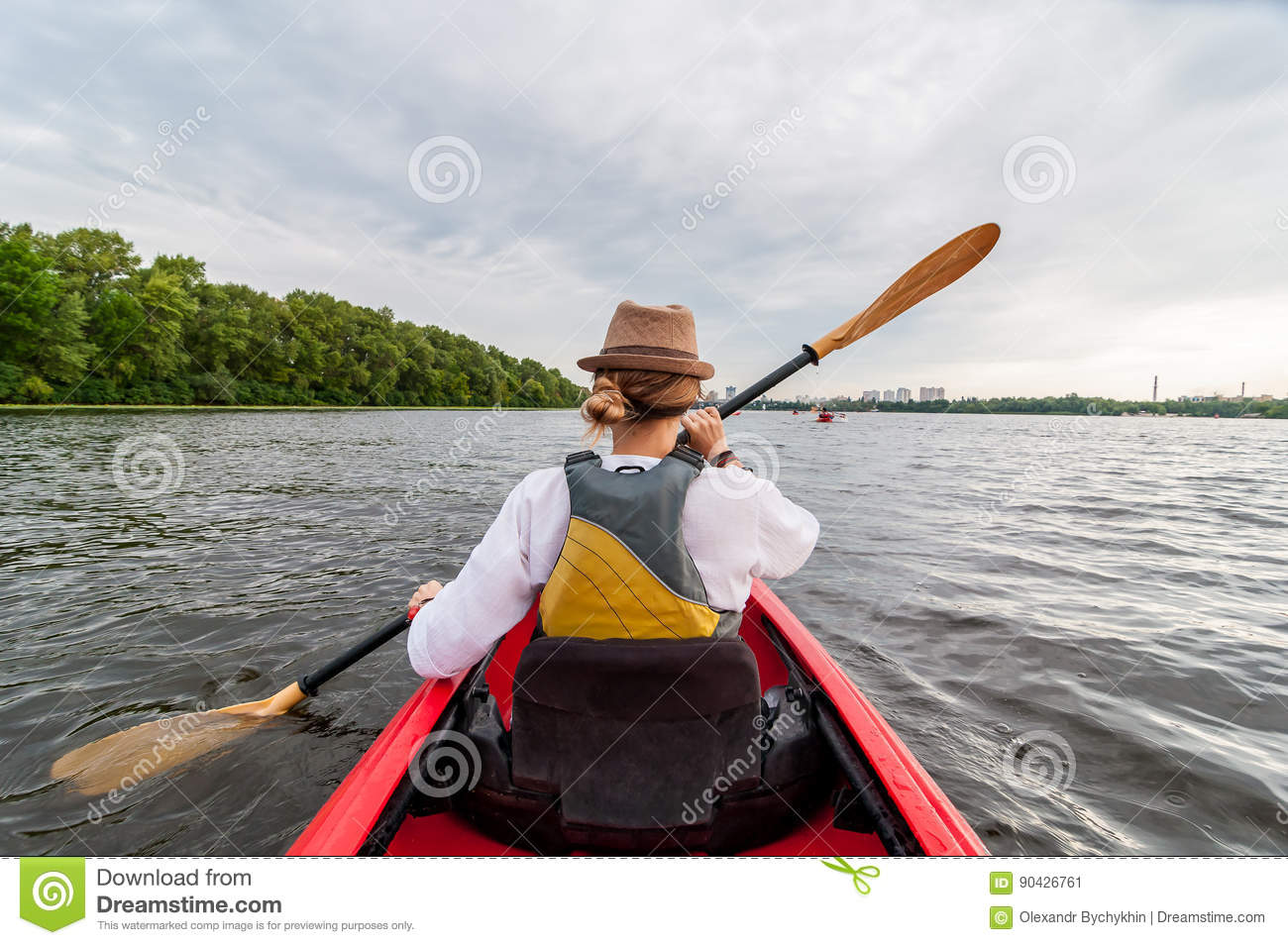 Kayaking travel. Young lady paddling the red kayak. Back view. Holiday and summer adventure