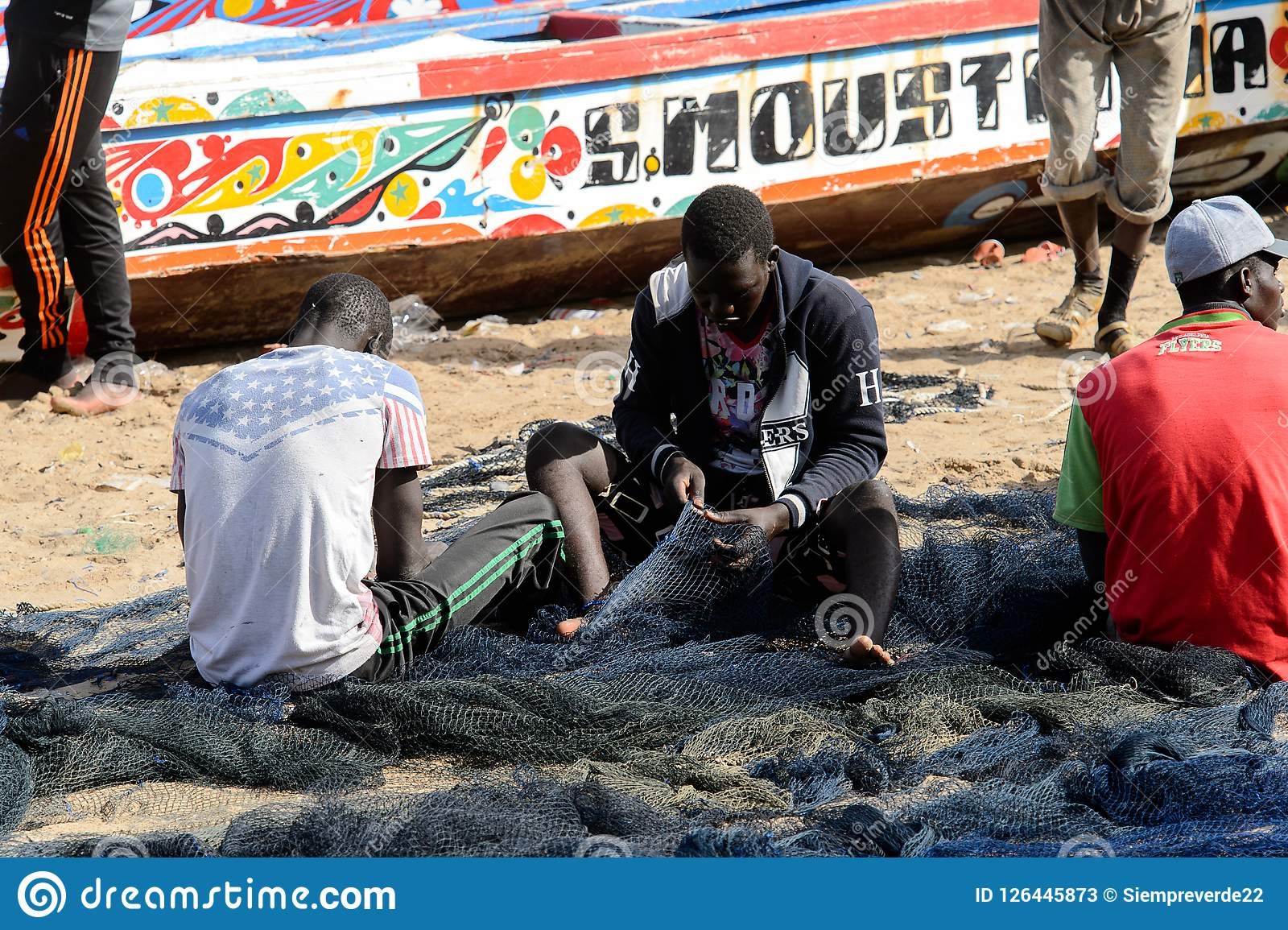 Unidentified Senegalese man sews a fishing net on the coast of
