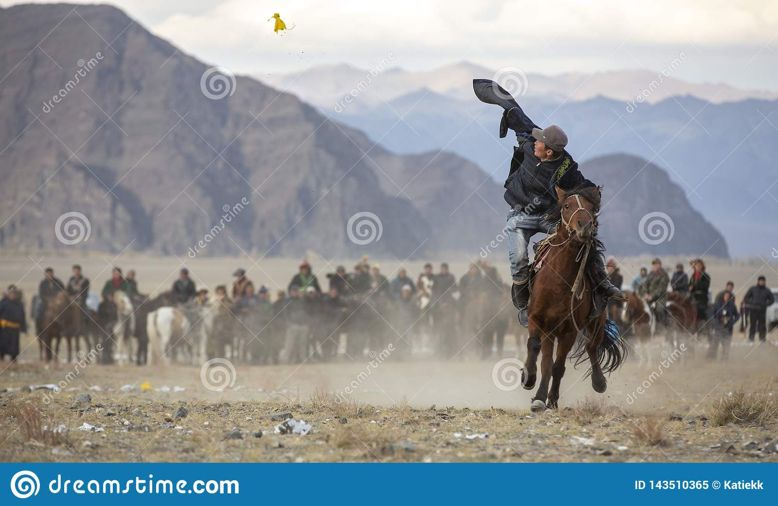 Kazakh man on a horse picking up coins from a ground