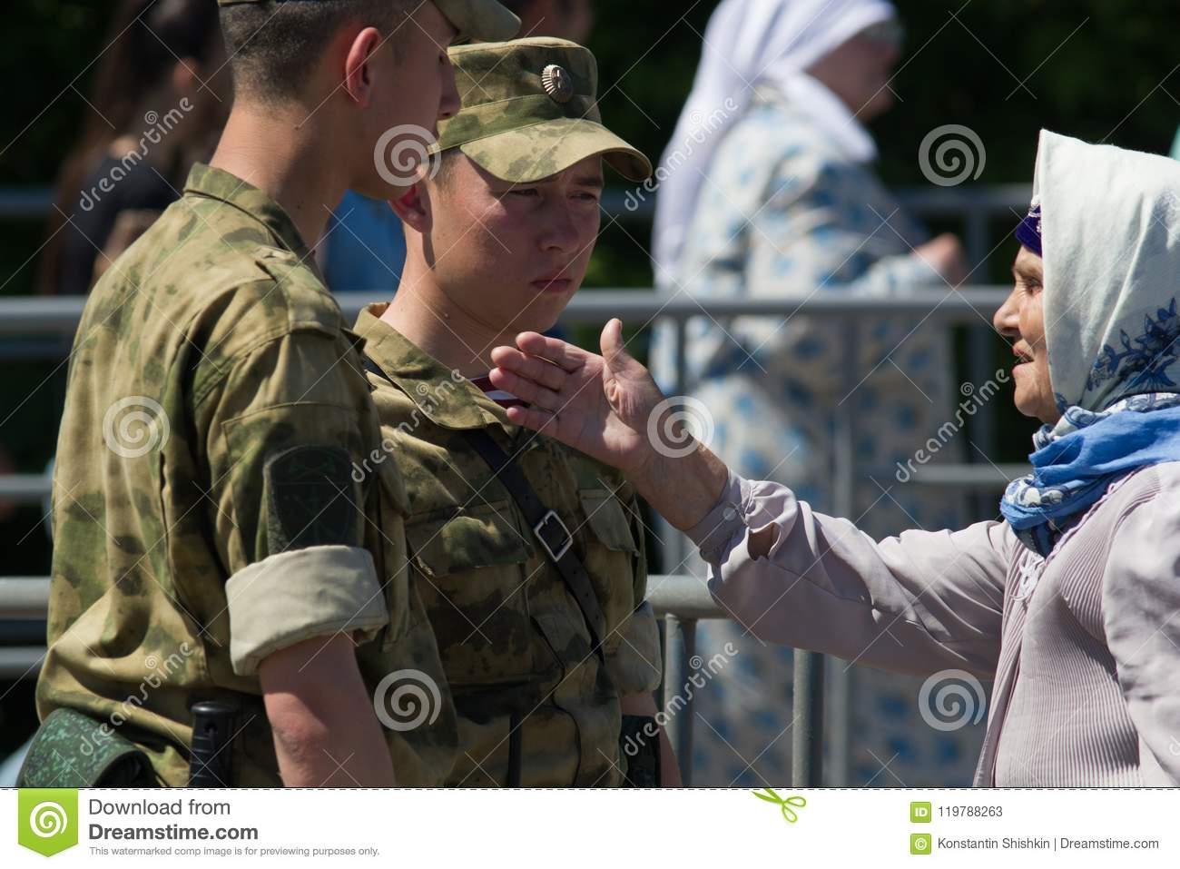 KAZAN, RUSSIA - JUNE 23, 2018: Traditional Tatar festival Sabantuy - Cute old woman in a scarf talking to young soldiers
