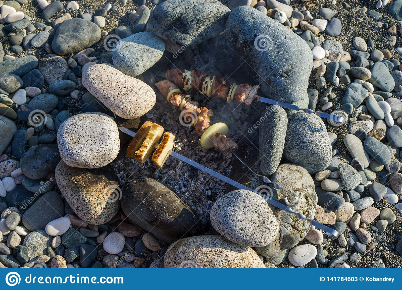 Kebab and bread are fried on the rocks on the rocky shore