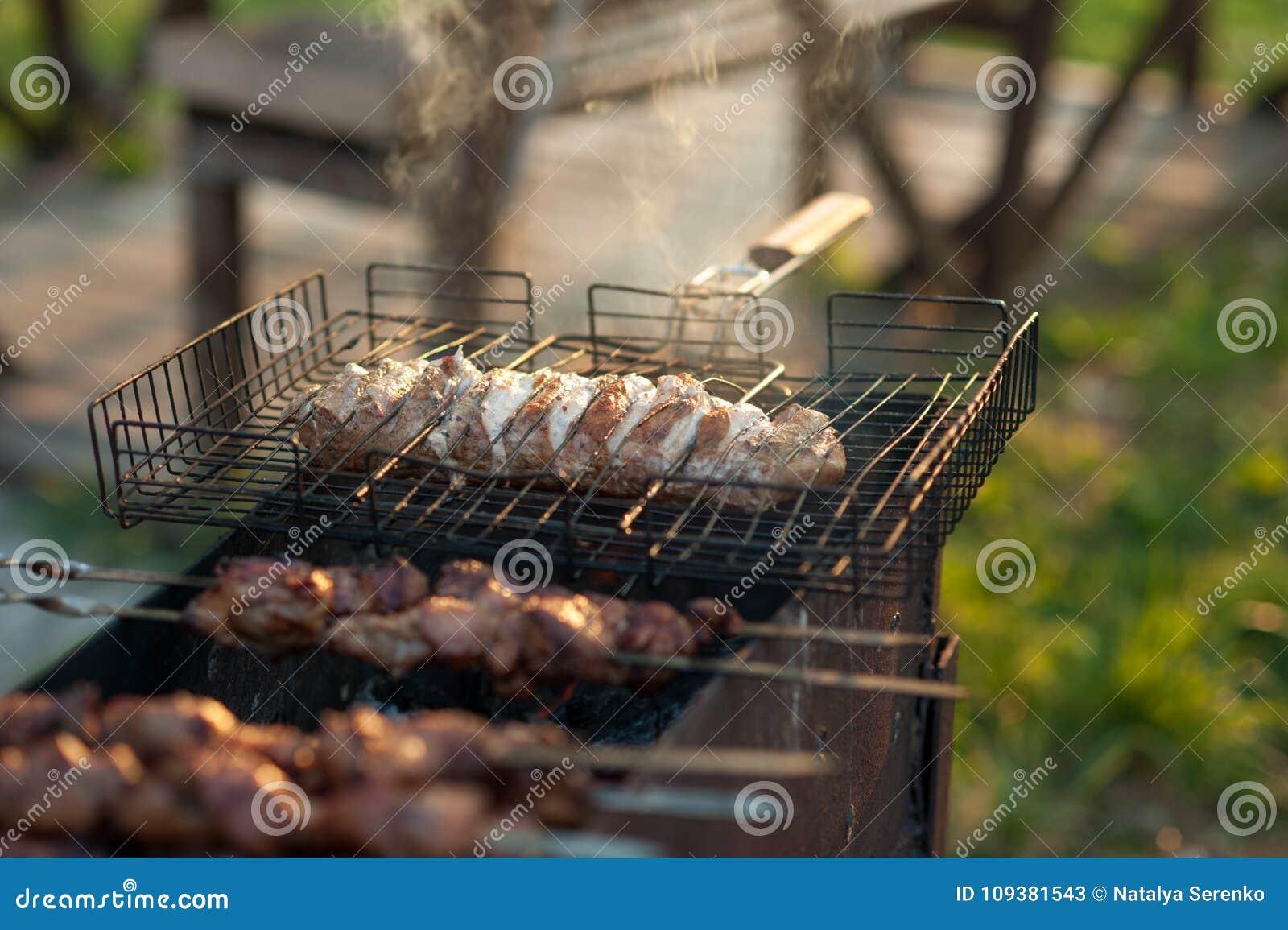Kebab en la parrilla Shashlik adobado que se prepara en una parrilla de la barbacoa sobre el carbón de leña