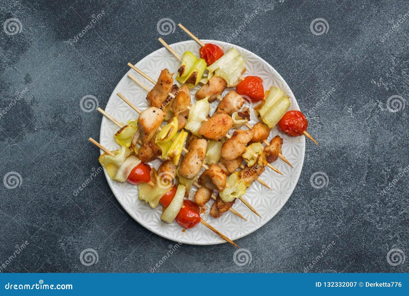 Kebabhöna, zucchini och tomater på steknålar i en platta Mörkt tabellkopieringsutrymme